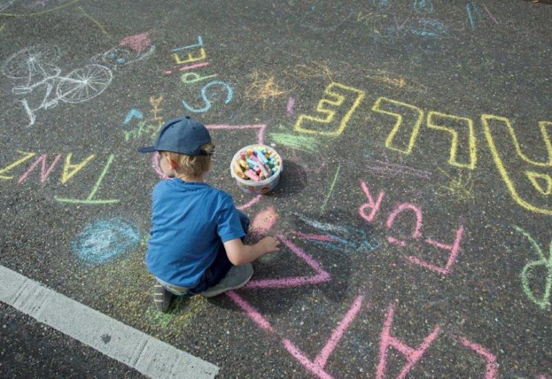 Kind malt auf der Straße mit Straßenkreide