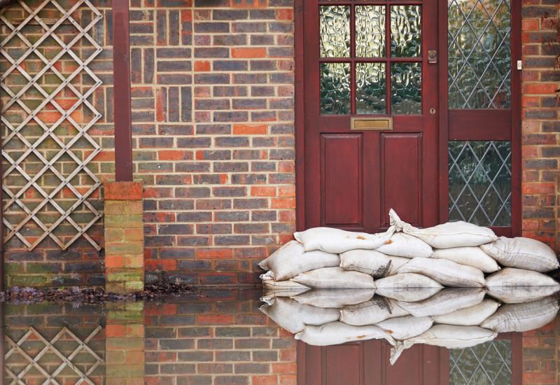 Sandsäcke wurden vor einer Haustür aufgestapelt, um das Haus vor Hochwasser zu schützen