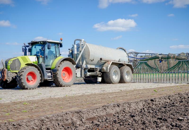 Foto: Ackerfläche mit Traktor und Schleppschlauchapplikator.