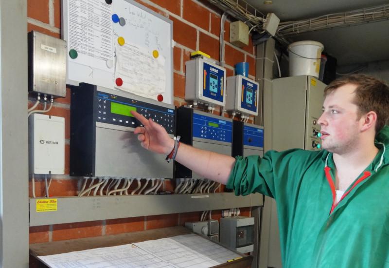 Landwirt in Schutzkleidung vor Anzeigetafel eines digitalen Monitoringsystems.