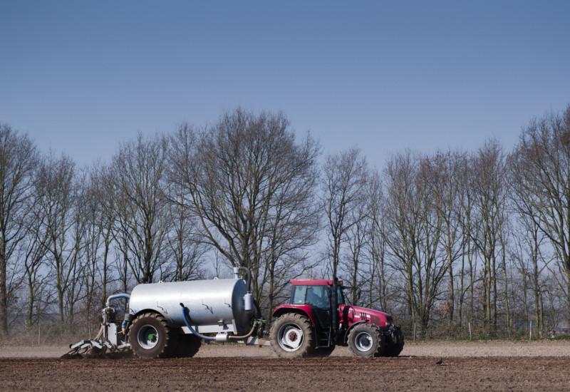 Großaufnahme eines Traktors, der auf einem Feld Gülle ausfährt