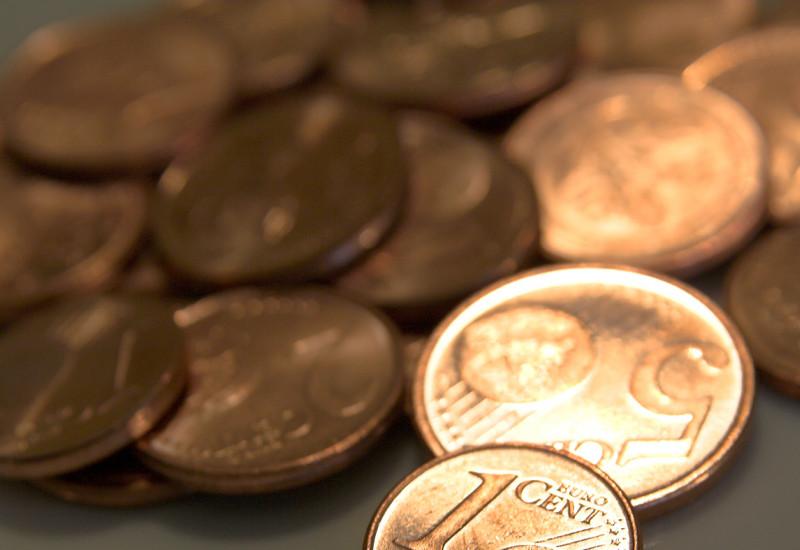 ein Haufen Kleingeld mit 1 Cent-Stück im Vordergrund