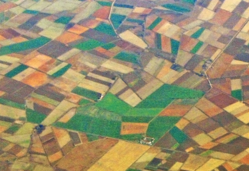 Bird's eye view of geometrical arranged, colourful fields and settlements