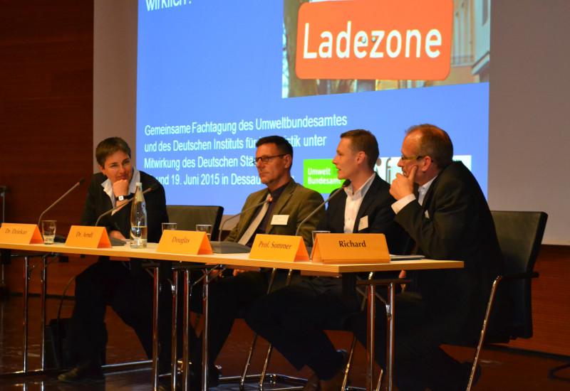 auf einem Podium sitzen drei Männer und eine Frau hinter Mikrofonen