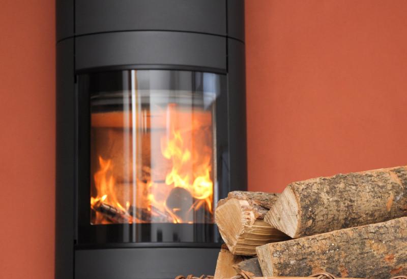 Kaminofen mit Feuer und Brennholzkorb