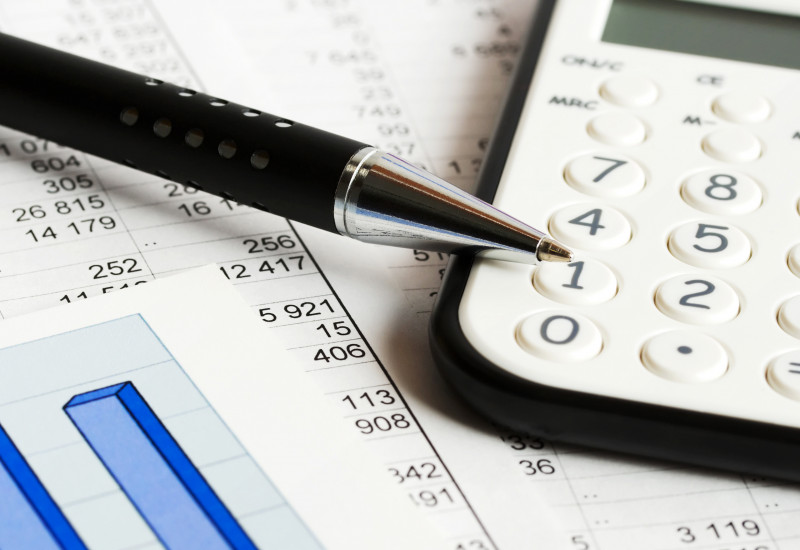 Das Bild zeigt einen Stift und einen Taschenrechner, die auf einem Ausdruck mit Tabellen und Diagramm liegen.