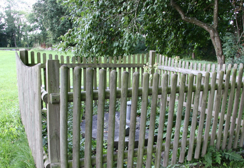 Umzäunter Brunnen mit Holzlatten auf grüner Wiese in Großaufnahme.