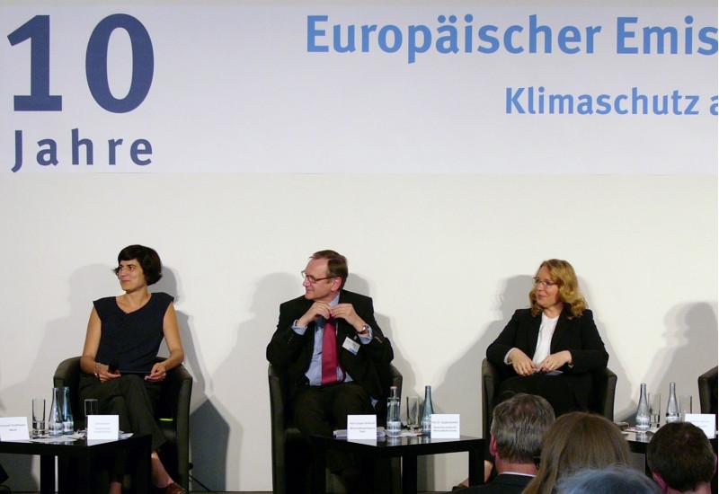 """drei Frauen und zwei Männer sitzen auf einem Podium und diskutieren. Auf einem Banner darüber steht """"10 Jahre Europäischer Emissionshandel"""""""
