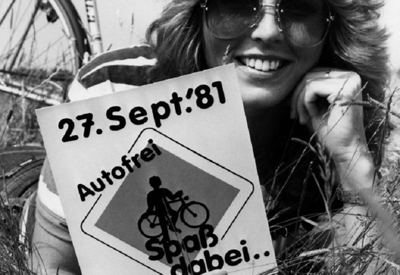 """eine Frau lmit Sonnenbrille iegt neben ihrem Fahrrad auf einer Wiese und hält ein Schild in die Kamera: 27. Sept.´81, Autofrei – Spaß dabei"""""""