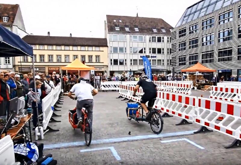 Zwei Lastenradfahrende treten auf dem Marktplatz in Würzburg gegeneinander an. Absperrung ist zu sehen.