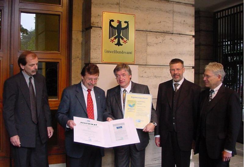 Gruppenfoto: fünf Männer im Anzug vor einem Gebäudes des Umweltbundesamtes, zwei halten ein Zertifikat und eine Urkunde in die Kamera