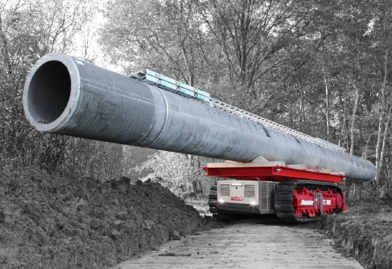 ein kleines selbstfahrendes Raupenfahrzeug transportiert auf seiner Ladefläche einen großen Betonmast durch den Wald