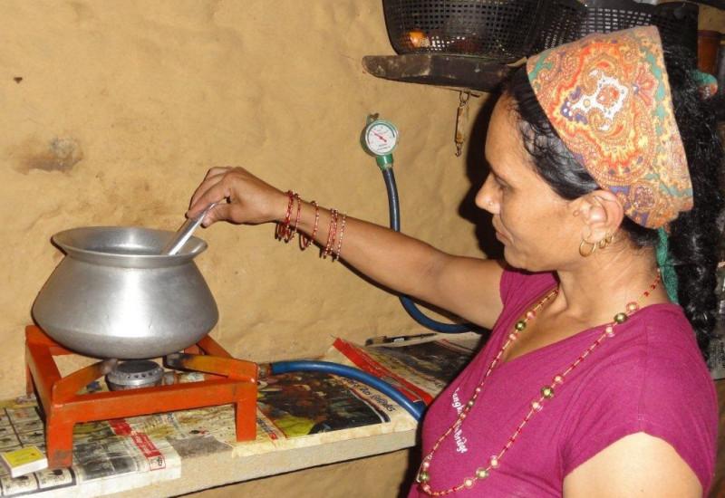 eine Frau in Nepal kocht zuhause auf einem kleinen Gaskocher