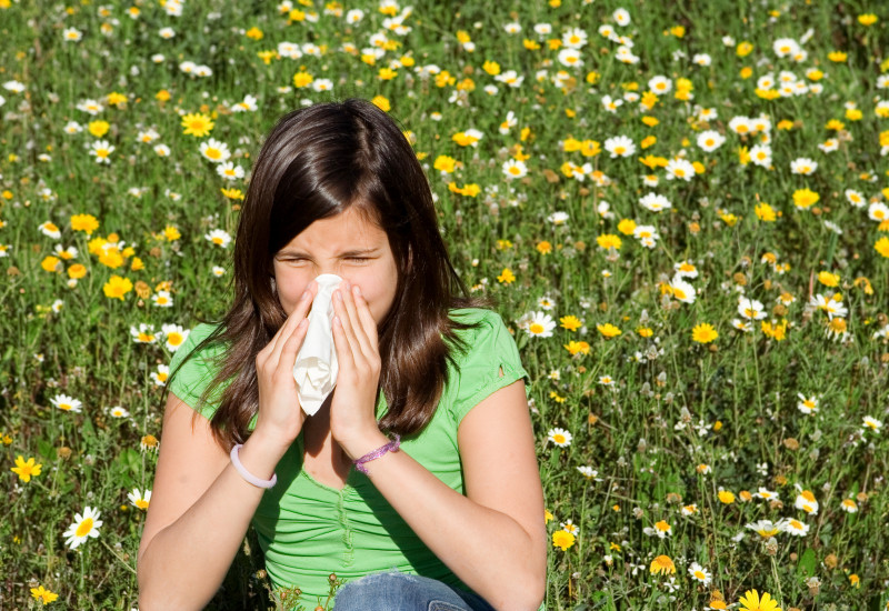 ein Mädchen sitzt auf einer Blumenwiese und schnaubt in ein Taschentuch