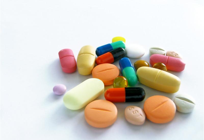 Tabletten in verschiedenen Formen und Farben liegen auf einem weißen Untergrund