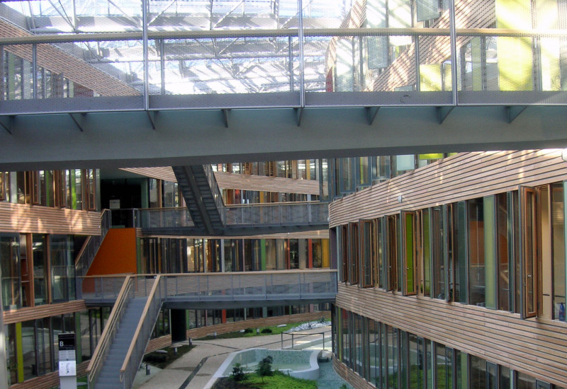 atrium with a glass roof, bridgesElongated inner courtyard with glass roof, skywalks linking two sides of the building, greenery and water basin