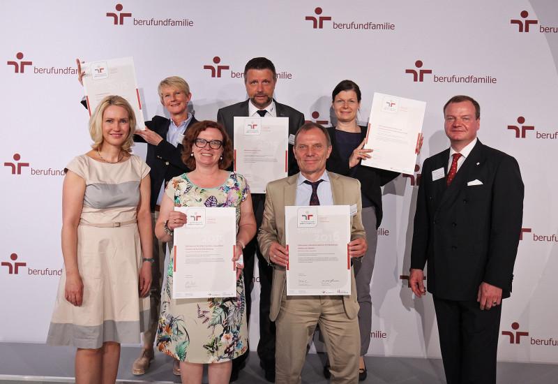 """Gruppenfoto, die Personen halten das Zertifikat """"Audit Beruf und Familie"""" 2015 in die Kamera"""
