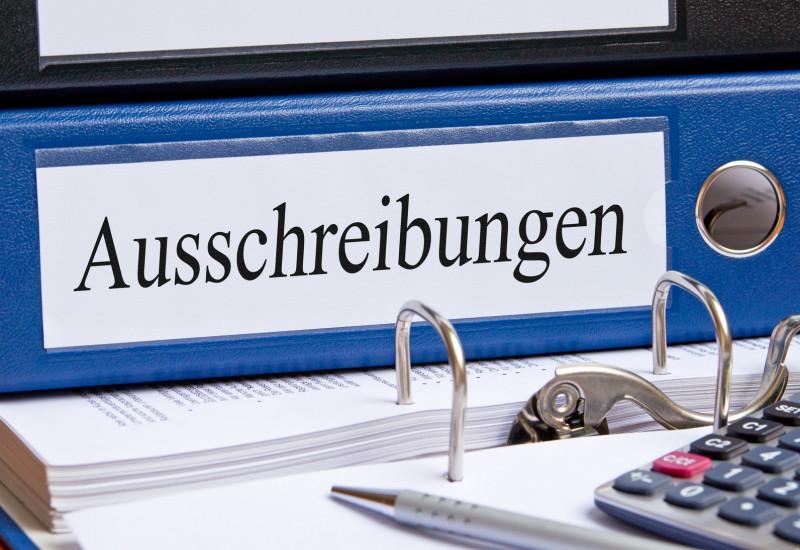 """auf einem Tisch liegen ein Ordner mit der Aufschrift """"Ausschreibungen"""", ein Taschenrechner und ein Kugelschreiber"""