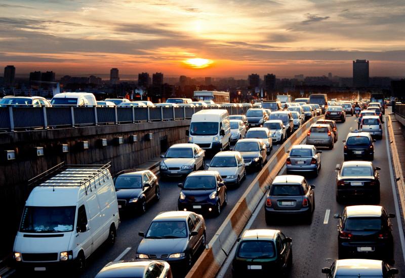 Autos im Stau, im Hintergrund eine Stadt und eine auf- oder untergehende Sonne