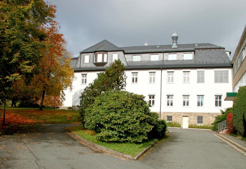 vierstöckiger weißer Altbau mit einer Auffahrt durch eine Grünanlage, rechts ein dreistöckiger älterer Neubau