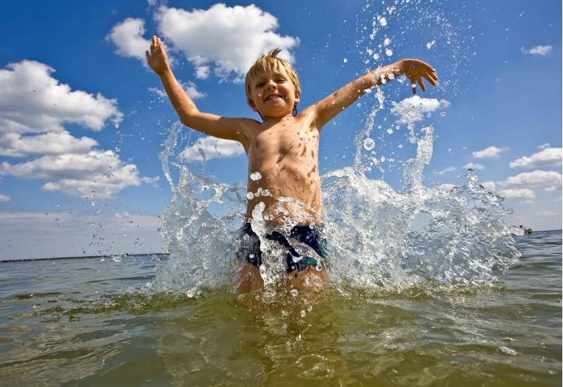 ein kleiner Junge tobt lachend im Meer oder in einem großen Badesee