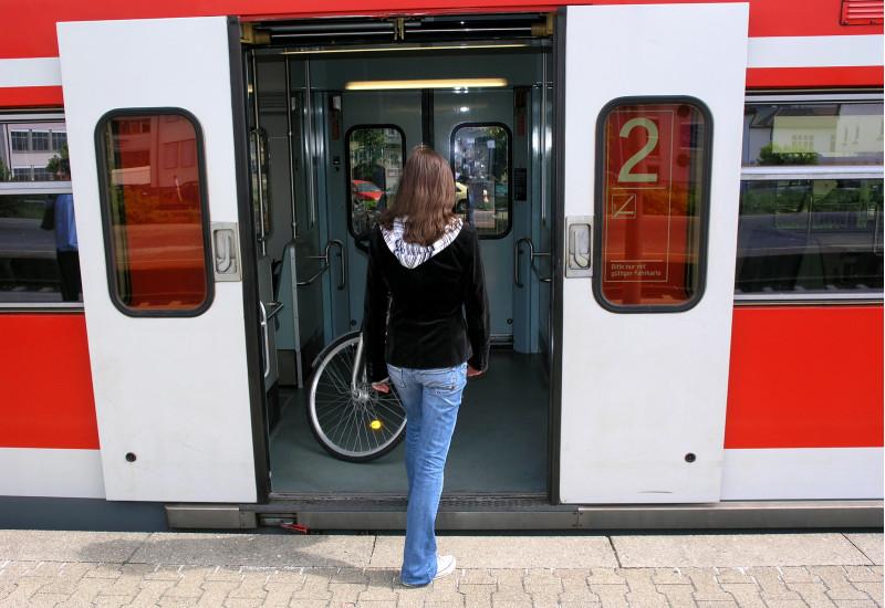 eine junge Frau steigt in eine Regionalbahn, in der sich ein Fahrrad befindet