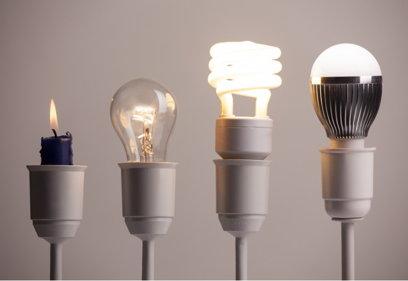 vier Lampenfassungen in einer Reihe, darin stecken (von links nach rechts): eine Kerze, eine Glühlampe, eine Energiesparlampe (Kompaktleuchtstofflampe), eine LED-Lampe