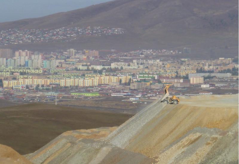 riesige, terrassierte Halde aus Gestein vor einer am Berg gelegenen Stadt mit Hochhaussiedlungen. Ein Muldenkipper kippt weiteres Material ab.