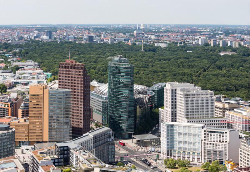 """der Potsdamer Platz mitz seinen Hochhäusern und die große waldartige Grünanlage """"Großer Tiergarten"""" in Berlin von oben gesehen"""