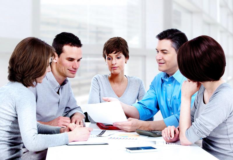 Zwei Männer und drei Frauen sitzen an einem Tisch in einem Büro zu einer Besprechung