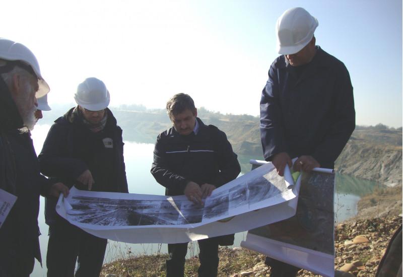 5 Männer mit Schutzhelmen stehen vor einem sehr großen wassergefüllten Rückhaltebecken und schauen Pläne an