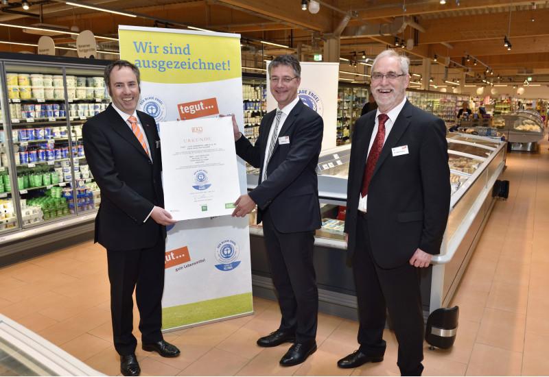 """drei Männer in Anzügen stehen nebeneinander in einem Supermarkt und lächeln in die Kamera, zwei halten gemeinsam eine Urkunde mit dem """"Blauen Engel"""" darauf , im Hintergrund ein Plakat mit dem """"Blauen Engel"""" und der Aufschrift """"Wir sind ausgezeichnet!"""""""