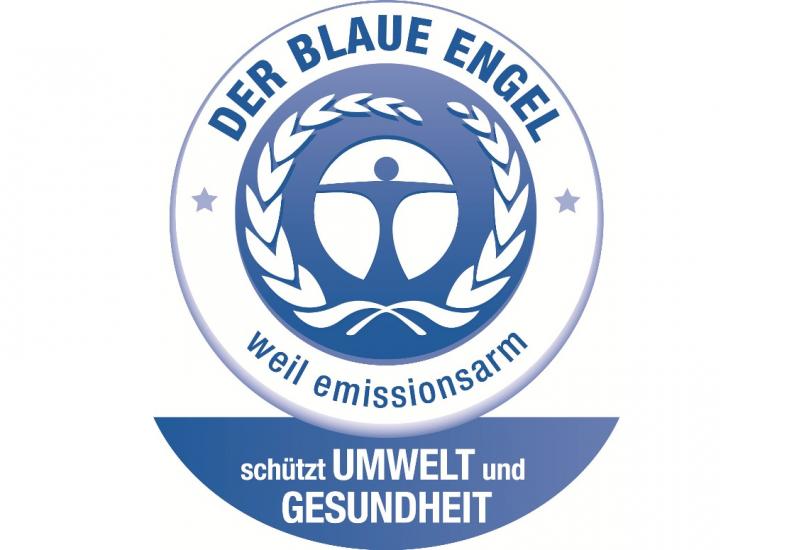 ein stilisierter blauer Mensch in einem weiß-blauen Kreis mit einem beblätterten Zweig und der Aufschrift: Der Blaue Engel - weil emissionsarm - schützt Umwelt und Gesundheit