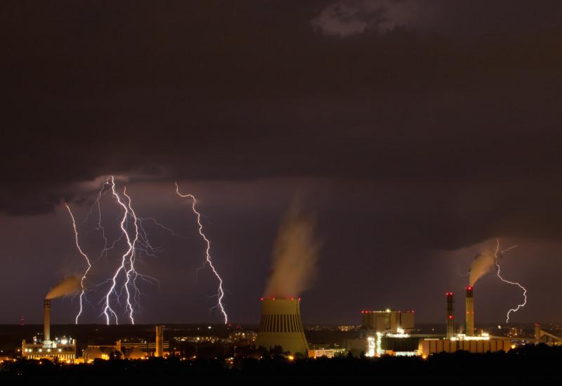 über einer Industrieanlage bei Nacht tobt ein Unwetter mit Blitzen und dunklen Wolken