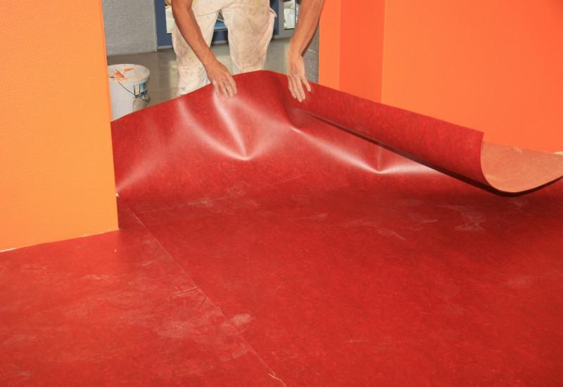Handwerker verlegt einen roten Fußbodenbelag