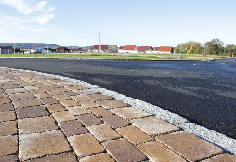asphaltic street and paved footway, in the background new houses
