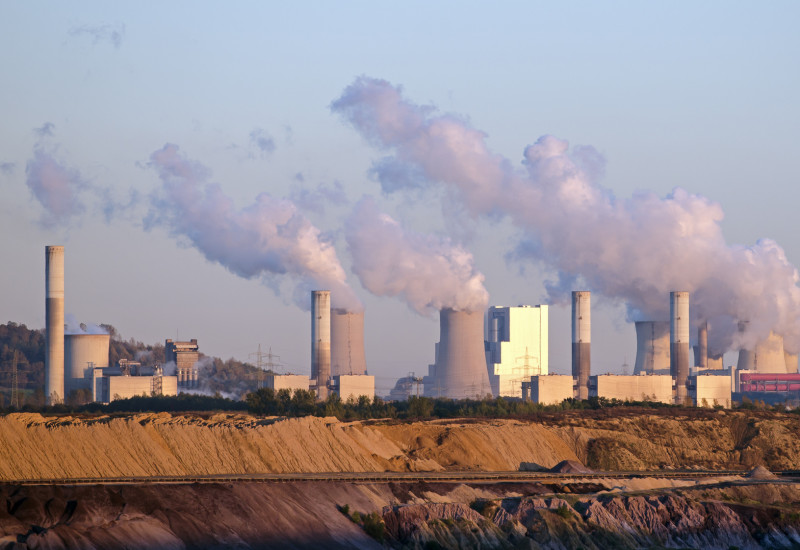Kraftwerk mit rauchenden Schornsteinen am Rande eines Tagebaus