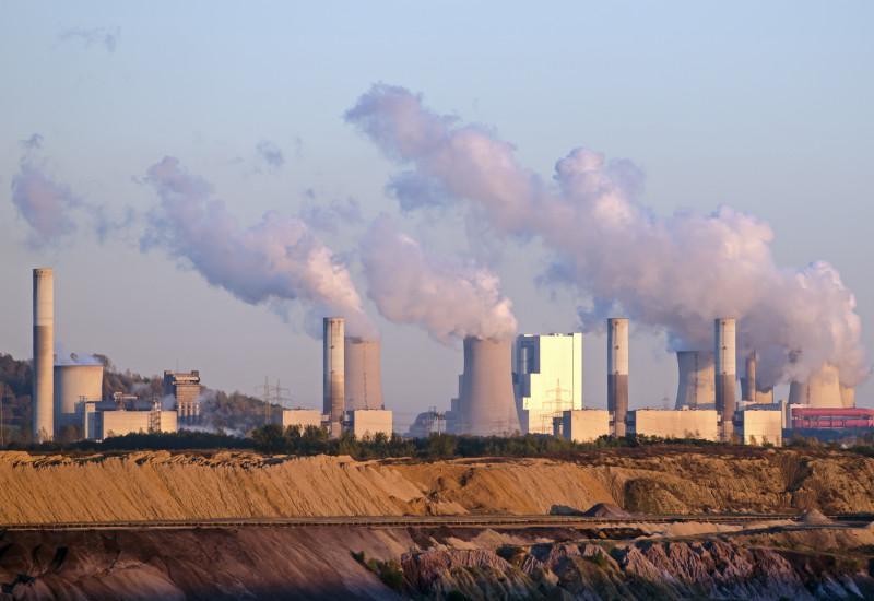 rauchende Schornsteine eines Braunkohlekraftwerks, davor ein Tagebau