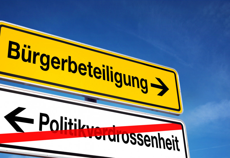"A road sign ""Bürgerbeteiligung"" (civic participation) and ""Politikverdrossenheit"" (disenchantment with politics)"