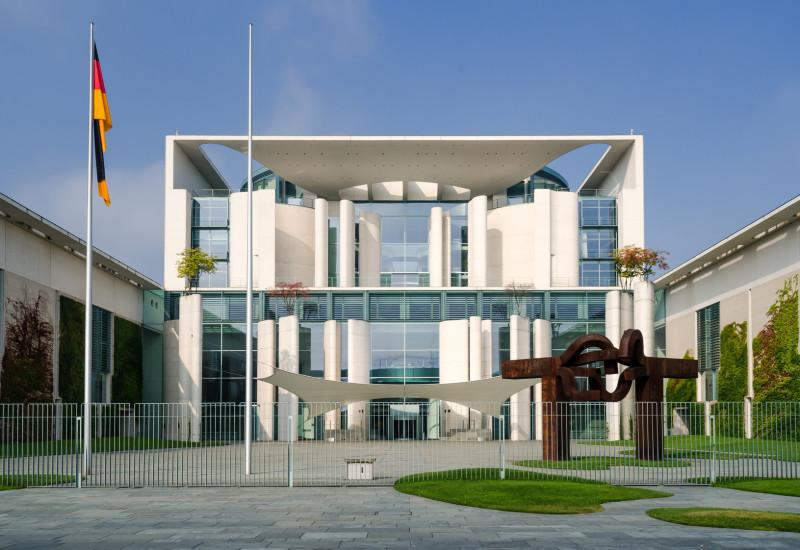 modernes weißes Gebäude mit Flachdach und großzügigem Eingangsbereich mit verglaster Fassade, davor eine deutsche Flagge und eine moderne Gartengestaltung mit amorphen kleinen Rasenflächen und modernen Skulpturen