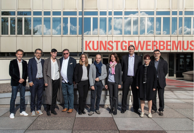 "group photo: 10 men and women in front of a building with the writing ""Kunstgewerbemuseum"""