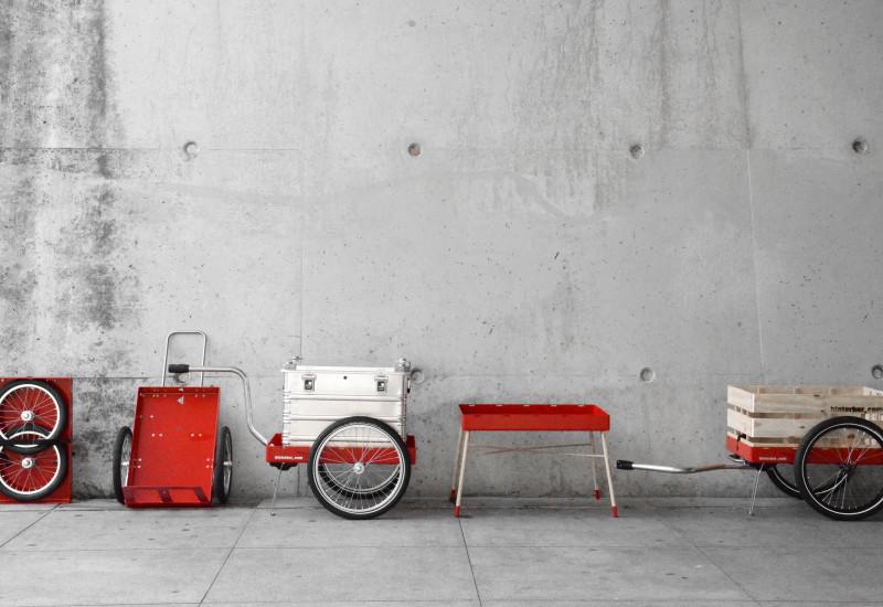 multifunktionaler Handwagen. Das Produkt steht in den fünf möglichen Aufbauvarianten nebeneinander vor einer Betonwand: platzsparend zusammengeklappt, als Trolley, als Handwagen mit Kiste, als Beistelltisch, als Fahrradanhänger.