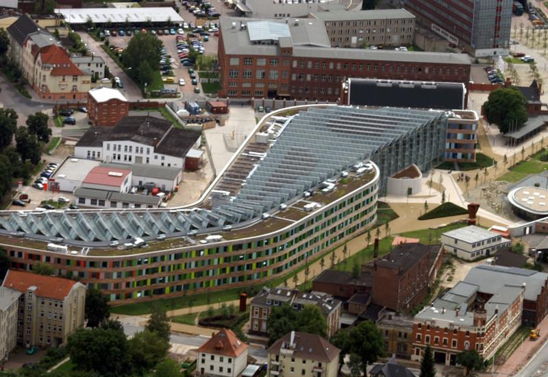 das UBA-Gebäude in Dessau-Roßlau von oben fotografiert, das Gebäude ist langgestreckt, hat eine Fassade aus Holt und bunten Glasplatten und schräggestellte Solarzellen auf dem gesamten Flachdach