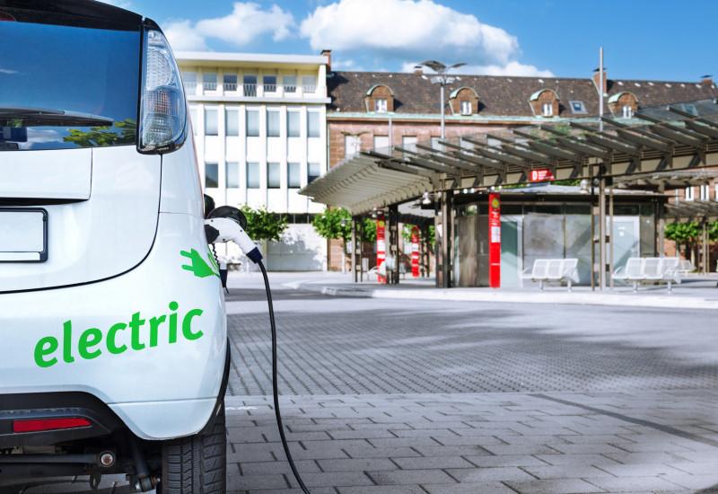 Ein Elektroauto wird aufgeladen, im Hintergrund eine moderne Bushaltestelle in der Stadt