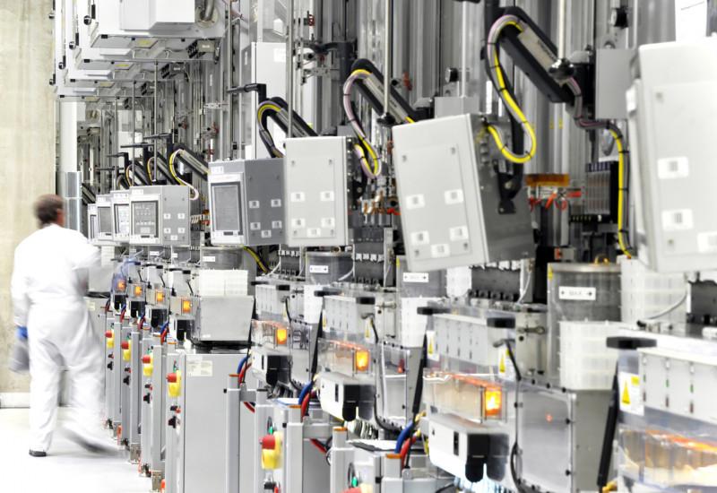 Arbeiter mit weißem Schutzanzug in der Werkhalle einer Chipfabrik mit vielen Geräten