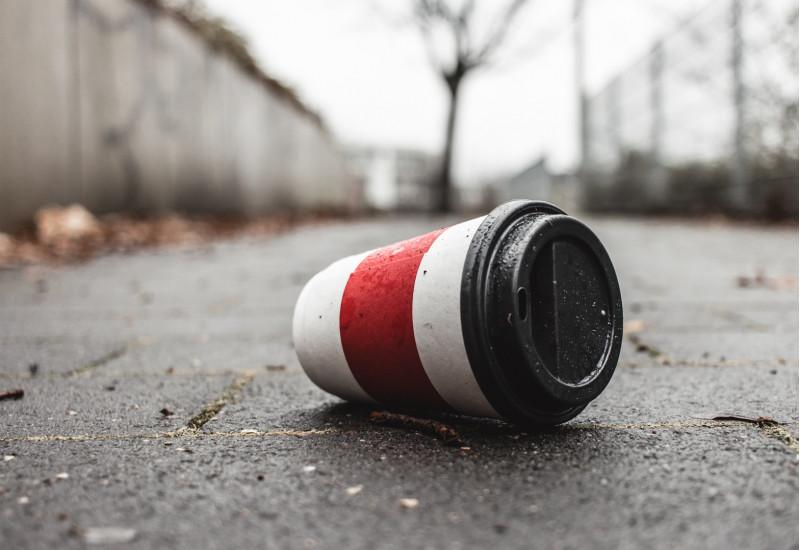 ein weggeworfener Coffee-To-Go-Pappbecher mit Plastikdeckel liegt auf einem Gehweg in der Stadt