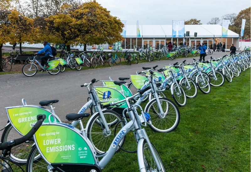 vor einem Gebäude stehen viele gleiche Fahrräder mit dem Logo der 23. Weltklimakonferenz in einer Reihe