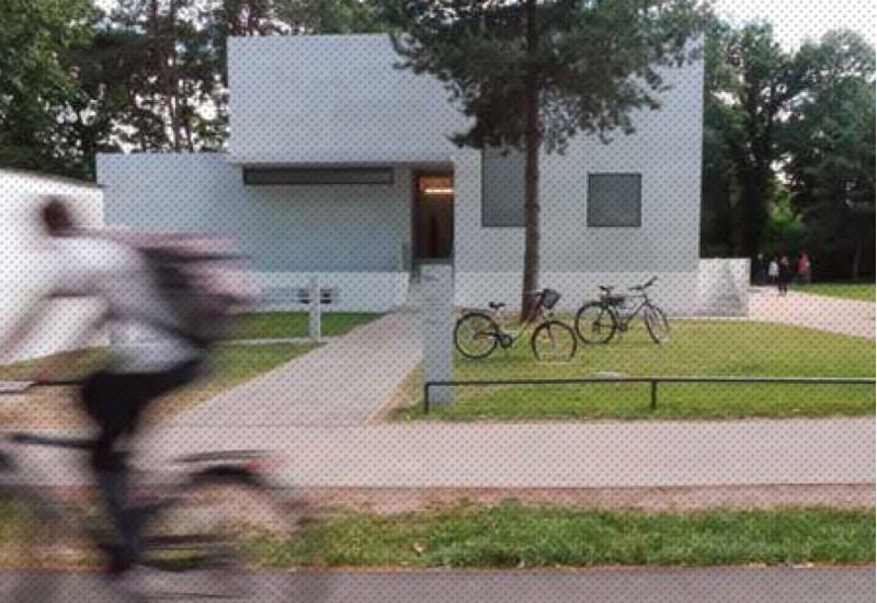 vor einem weißen kleinen Haus im Bauhausstil stehen zwei Fahrräder auf dem Rasen und ein Radfahrer fährt vorbei