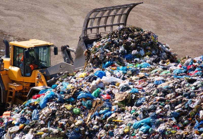 Radlader türmt Abfälle auf einer Deponie zu einem Berg auf