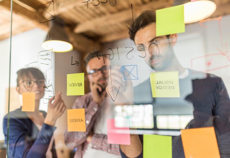 drei junge Kreative diskutieren ihre Planung und dafür haben Zettel an eine Glaswand geklebt